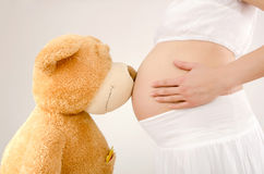 Close up on pregnant belly and a big teddy bear. Stock Photography