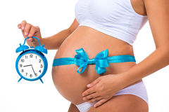 Close-up of a pregnant belly with a blue ribbon and an alarm clock. Concept of pregnancy stock images