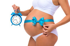 Close-up of a pregnant belly with a blue ribbon and an alarm clock. Concept of pregnancy Royalty Free Stock Images