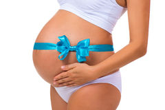 Close-up of pregnant belly with blue ribbon and bow. Concept of pregnancy. Newborn baby boy stock images
