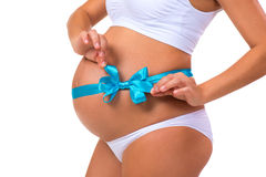 Close-up of pregnant belly with blue ribbon bow for newborn baby boy. Concept of pregnancy.  stock image