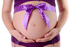Close up of pregnant belly decorated with ribbon Royalty Free Stock Images