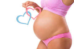 Close-up of a pregnant belly with pink and blue hearts. Royalty Free Stock Photos