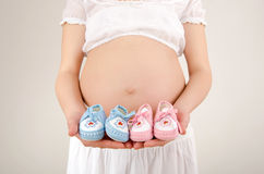 Close up on pregnant belly with pink and blue new born shoes.. Stock Images