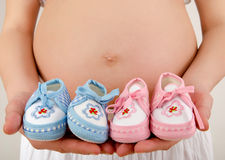 Close up on pregnant belly with pink and blue new born shoes.. Stock Photo