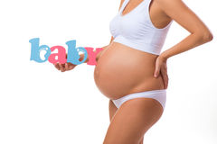 Close-up of a pregnant belly with a sign baby. Royalty Free Stock Images