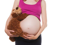 Close up on pregnant belly with toy. Woman Stock Photo