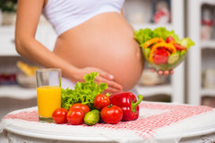 Close-up of a pregnant belly. Women's Health, fortified food. Fresh vegetables, diet and figure.  Royalty Free Stock Photography