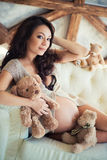 Close-up of a pregnant girl with brown teddy bear sitting on the couch Royalty Free Stock Photography