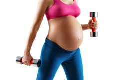 Close up of pregnant woman with beautiful healthy body holding dumbbells isolated on white background. Concept of healthy life stock image