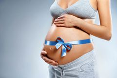 Close up of pregnant woman with blue ribbon touching her belly on grey background. Pregnancy, maternity, preparation and expectation concept stock photography