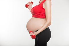 Close up of pregnant woman doing exercise with. Pregnant woman doing exercise with red dumbbells stock photo