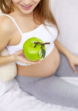 Close up of pregnant woman eating apple at home Stock Image