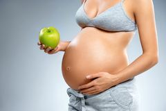 Close up of pregnant woman with green apple and touching her belly on grey background. Pregnancy, maternity, preparation and expectation concept stock photography
