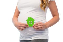 Close up of pregnant woman with green house icon. Pregnancy, ecology, people and housing concept - close up of pregnant woman with green house icon Stock Photos