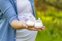 Close up of pregnant woman hand with baby shoes Stock Images