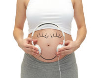 Close up of pregnant woman and headphones on tummy Stock Image