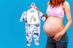 Close up of a pregnant woman holding baby dress. On blue background Stock Photo