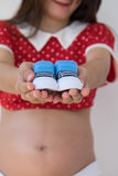 Close-up of a Pregnant Woman  holding Baby Shoes in  Hands. Stock Photo
