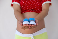 Close-up of a Pregnant Woman  holding Baby Shoes in  Hands. Stock Photography
