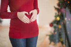 Close up of a pregnant woman making a heart on her belly Stock Images