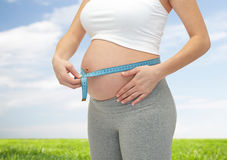Close up of pregnant woman measuring her tummy Royalty Free Stock Photos
