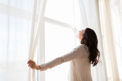 Close up of pregnant woman opening window curtains Royalty Free Stock Photo