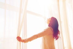 Close up of pregnant woman opening window curtains Stock Image