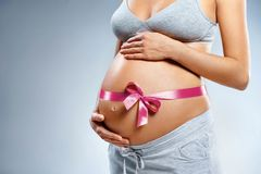 Close up of pregnant woman with pink ribbon touching her belly on grey background. Pregnancy, maternity, preparation and expectation concept royalty free stock image