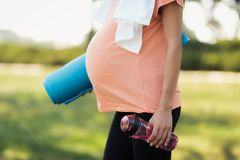 Close up. Pregnant woman in pink t-shirt with sports bottle and yoga mat in hands royalty free stock image