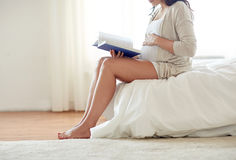 Close up of pregnant woman reading book at home Stock Photography