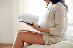Close up of pregnant woman reading book at home Royalty Free Stock Photos