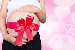 Close up pregnant woman with red ribbon gift on belly on heart b Royalty Free Stock Image