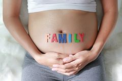 Close up Pregnant woman sitting on soft sofa and touching her belly with sign FAMILY in front of her belly royalty free stock photo
