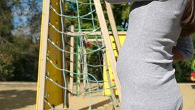 Pregnant girl on the playground, close-up. Close-up of a pregnant woman stroking her large belly against the background of a playground and a children`s roller stock video footage
