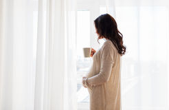 Close up of pregnant woman with tea cup at window. Pregnancy, drinks, rest, people and expectation concept - close up of happy pregnant woman with cup drinking Royalty Free Stock Images