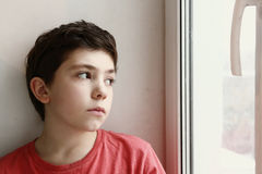 Close up preteen boy portrait look at the window royalty free stock photography