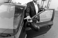 Close up preto e branco do gerente de vendas do carro que guarda a chave disponível Fotos de Stock Royalty Free