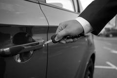 Close up preto e branco do homem que introduz a chave do carro no furo Fotografia de Stock
