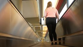 Close up of pretty attractive woman riding on conveyor belt in airport terminal - low angle. July 29 2018 stock video footage