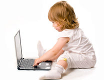 Close-up of pretty baby working at laptop. Isolated over white Royalty Free Stock Images