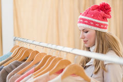 Close up of a pretty blonde looking at clothes on rail Stock Images