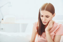 Close up of pretty disappointed woman which having toothache. Unstoppable pain. Beautiful brunette woman grimacing and touching her jowl while having toothache royalty free stock images