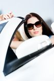 Close up of pretty female driver. In the white cabriolet Stock Image