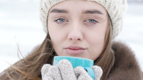 Close up of pretty girl drinking a cup of hot beverage outdoor in winter day stock video footage