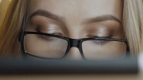 Close up of pretty girl in glasses using tablet in cafe. Slowly.  stock video