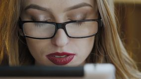 Close up of pretty girl in glasses using tablet in cafe. Slowly.  stock footage