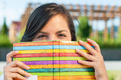 Close-up of pretty girl hiding behind notebook Royalty Free Stock Image