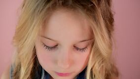 Close-up pretty little girl with blond hair and long eyelashes with blue eyes