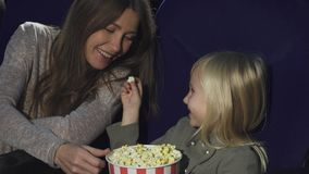 Adorable little girl feeding her mom with popcorn at the cinema royalty free stock image
